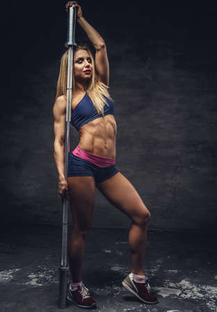 fullbody: Fullbody portrait of fitness blond female with barbell grif.