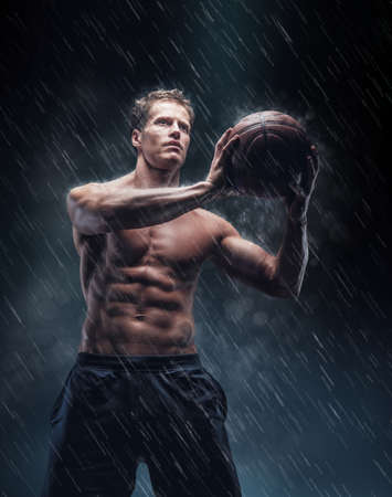 rain wet: Artistic portrait of shirtless wet bascetball player under droplets.