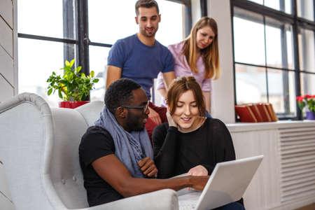 Multi ethnic student using laptop in apartments.