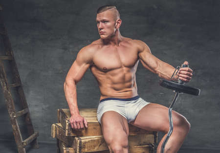 suntanned: Awesome suntanned muscular male sitting on a wooden boxes and holding barbell in one arm. Stock Photo