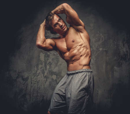 sixpack: Portrait of muscular shirtless male on grey background.