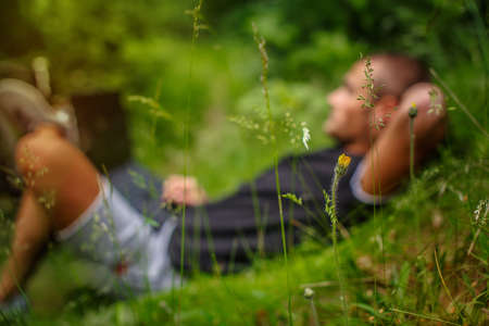 Caucasian male lying on a grass and using laptop. Stock Photo