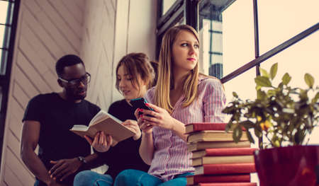 blackman: African american male and two caucasian females reading a book near window.
