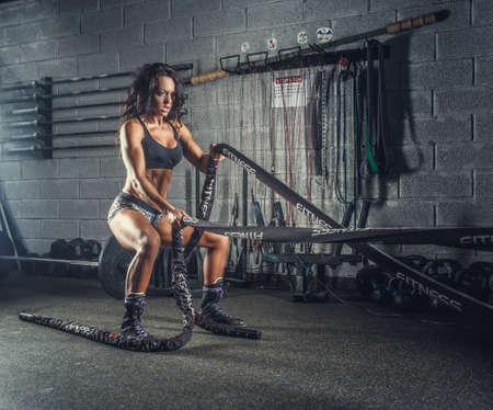 체육 피트 니스 모델 체육관 클럽에서 전투 로프와 함께 운동.