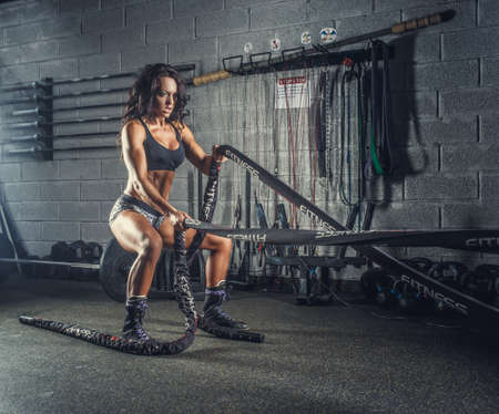 Female fitness model exercising with battle rope in a gym club.
