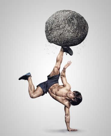cabeza abajo: Sin camisa masculina deportiva al revés con piedra gris en su pierna.