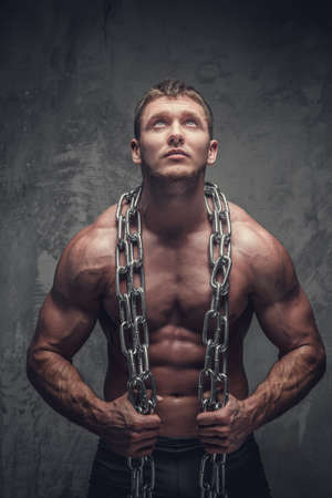 suntanned: Shirtless muscular suntanned male holding big chain on his neck.