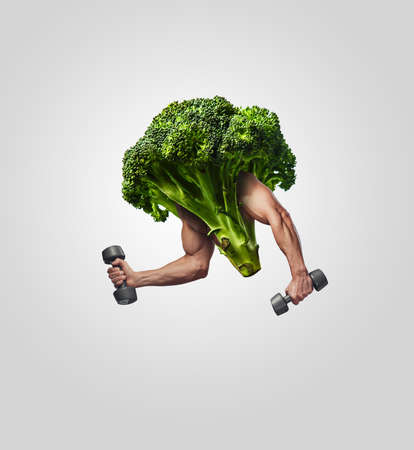Broccoli with muscular mans hands and dumbbells. Stock Photo
