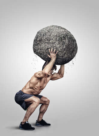 Shirtless muscular male doing squats with big stone.