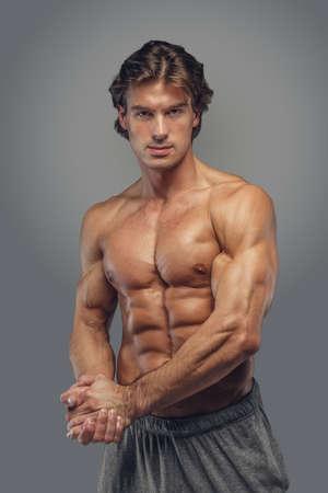 Suntanned shirtless geschiktheids mannelijk model dat op een grijze achtergrond wordt geïsoleerd. Stockfoto