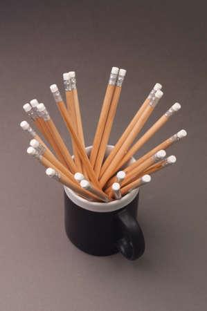 grafito: lápices de grafito en una taza negro sobre fondo gris.