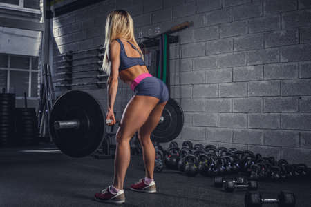 fullbody: Fullbody portrait of fitness blond female from back with barbell. Stock Photo