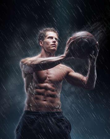 sotto la pioggia: giocatore di basket petto nudo sotto gocce di pioggia.