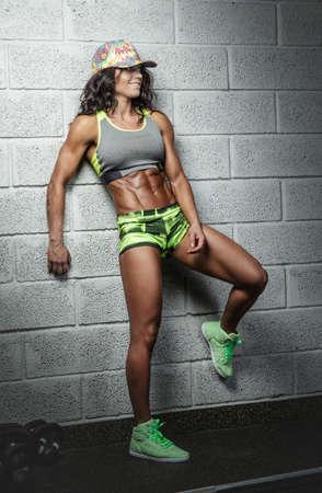 suntanned: Suntanned abdominal female fitness model posing over grey bricks wall. Stock Photo
