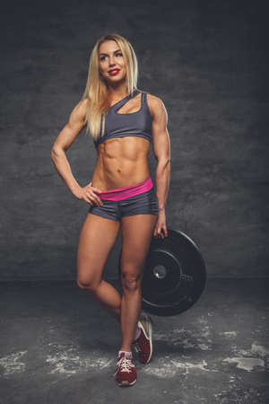 hottie: Blond female fitness model holding barbell weight on a grey background in a studio.