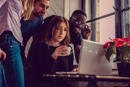 blackman: Multi ethnic student using laptop in apartments.