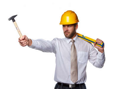 Professional worker in a shirt, yellow safety helmet holding hummer and level. Isolated on a white background.
