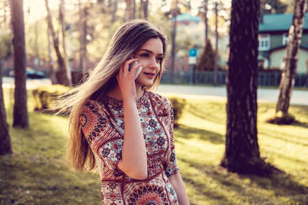 Awesome young female with smartphone in a summer wild park. Stock Photo