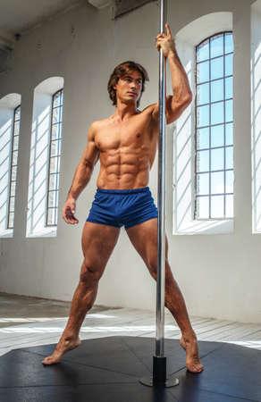 sixpacks: Portrait of sporty male near pole dance stand. Stock Photo