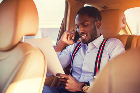 blackman: African american female in white shirt talking by smartphone and looking in to documents in a cars back seat.