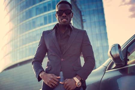Portrait of stylich african american male near car over skyscraper background. Stock Photo