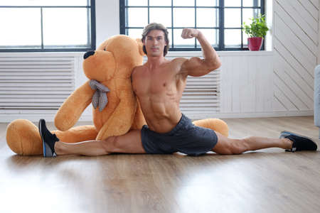 Flexible shirtless sporty male posing with big teddy bear on a floor.