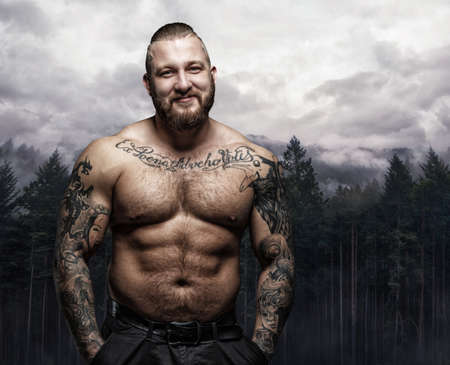 Positive shirtless tattooed male over nature background.