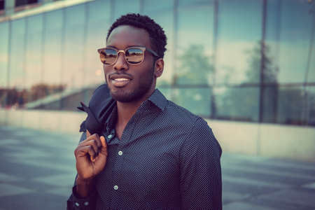 Casual african american male posing near modern building.