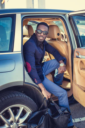blackman: Stylish african american male posing in a cars back seat.