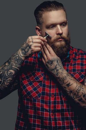 mâle Brutal avec bras tatoués à raser sa barbe.