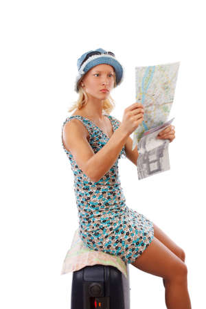 map case: Blond female in a hat and summer dress sitting on a travveling case and looking in to a map. Stock Photo