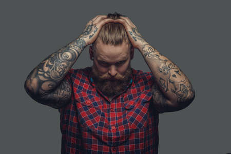 Portrait of bearded hipster with tattooes on his arms.