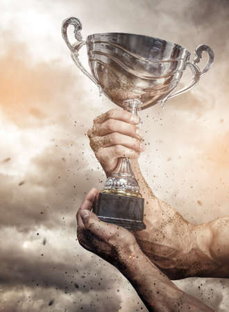 Cropped male arms with winner cup under cloudy sky. Stock Photo