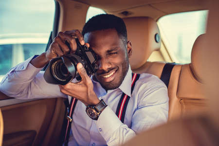 African american male in a white shirt shooting with dslr camera from cars back seat.