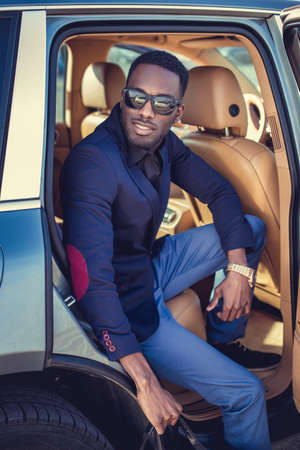 Stylish african american male posing in a cars back seat.
