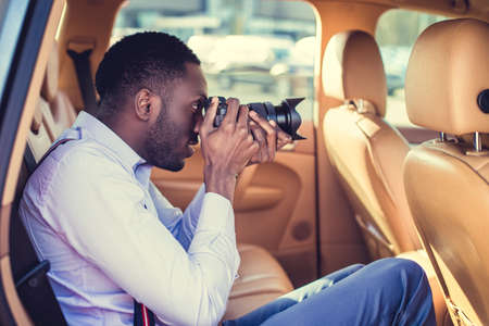 blackman: African american male in a white shirt shooting with dslr camera from cars back seat.