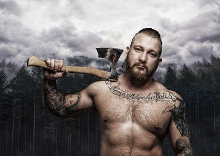 Shirtless tattooed viking holding axe over wild nature background. Stock Photo