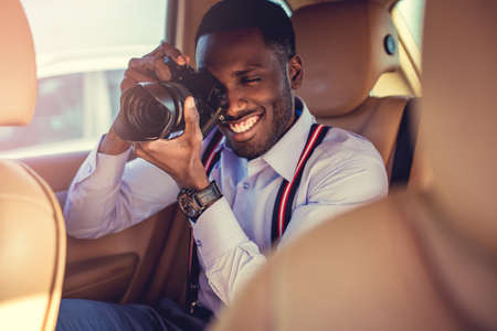 back seat: African american male in a white shirt shooting with dslr camera from cars back seat.