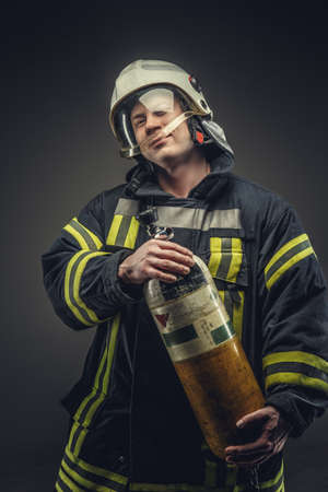 oxigen: Portrait of firefighter in safety uniform holding yellow oxigen tank. Stock Photo