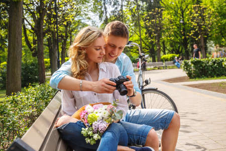 photocamera: Casual couple using compact dslr photocamera in summer park.