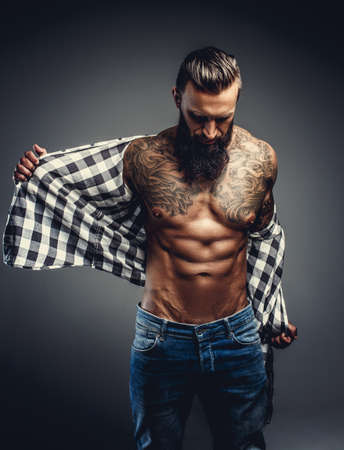 Tattooed bearded male taking off his shirt and undressing for studio shooting.