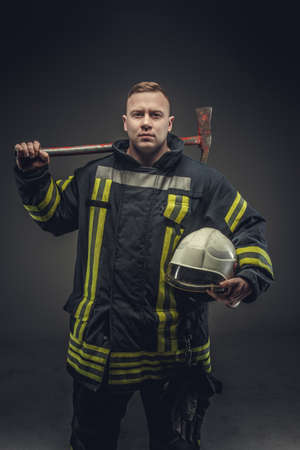 fireproof: Portrait of male in firefighter costume holding helmet and recue red axe. Stock Photo