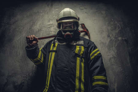 fireproof: Portrait of firefighter in oxygen mask holding red rescue axe. Stock Photo