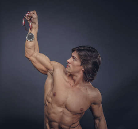 silver medal: Shirtless muscular male holding silver medal over grey background.
