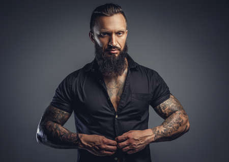 undressing: Tattooed bearded male taking off his shirt and undressing for studio shooting.