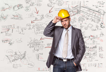 executive helmet: Project manager in a suit with hard yellow helmet over desk with drawnings.