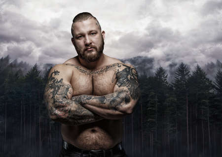 Shirtless tattooed male with crossed arms over wild nature background. Stock Photo