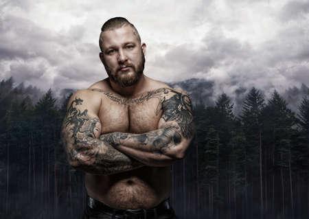 generosa: Sin camisa masculina tatuado con los brazos cruzados sobre el fondo la naturaleza salvaje.