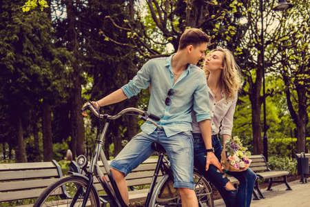 joyfull: Joyfull couple posing on one bicycle in a city summer park.