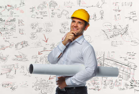 executive helmet: Positive engineer worker with drawning tube over working desk.